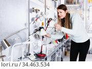 Portrait of young female trying to use desk lamp in furniture showroom. Стоковое фото, фотограф Яков Филимонов / Фотобанк Лори