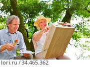 Senioren malen gemeinsam ein Bild in der Natur mit Staffelei und ... Стоковое фото, фотограф Zoonar.com/Robert Kneschke / age Fotostock / Фотобанк Лори