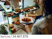 Barista takes croissant from showcase in cafe. Стоковое фото, фотограф Tryapitsyn Sergiy / Фотобанк Лори