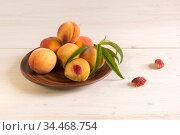 Спелые сочные персики в терракотовой тарелке на белом деревянном столе. Стоковое фото, фотограф Наталья Гармашева / Фотобанк Лори