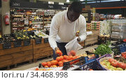 African American man shopping in organic food store, choosing fresh vegetables. Стоковое видео, видеограф Яков Филимонов / Фотобанк Лори