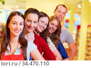 Supermarkt-Team steht lächelnd hintereinander in einer Reihe. Стоковое фото, фотограф Zoonar.com/Robert Kneschke / age Fotostock / Фотобанк Лори