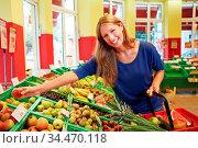 Lachende junge Frau greift nach Obst im Supermarkt. Стоковое фото, фотограф Zoonar.com/Robert Kneschke / age Fotostock / Фотобанк Лори