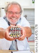 Lächelnder Arzt mit einem Stapel bunter Pillen in seinen Händen. Стоковое фото, фотограф Zoonar.com/Robert Kneschke / age Fotostock / Фотобанк Лори
