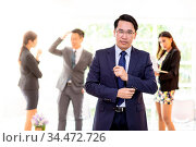 Portrait of asian businessman with business team in background at... Стоковое фото, фотограф Zoonar.com/Vichaya Kiatying-Angsulee / easy Fotostock / Фотобанк Лори