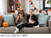 girls in halloween costumes with pumpkins at home. Стоковое фото, фотограф Syda Productions / Фотобанк Лори