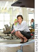 Frau im Büro hockt mit verschiedenen Unterlagen auf dem Boden. Стоковое фото, фотограф Zoonar.com/Robert Kneschke / age Fotostock / Фотобанк Лори
