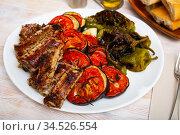 Grilled pork ribs rack garnished on white plate with eggplant, tomatoes and bell pepper. Стоковое фото, фотограф Яков Филимонов / Фотобанк Лори