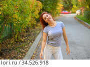 A beautiful red-haired woman is walking along the street and dancing. Happy girl in a gray T-shirt and striped leggings walks and has fun in the autumn park. Photo in motion. Стоковое фото, фотограф Михаил Решетников / Фотобанк Лори