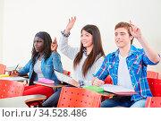 Drei Schüler in der Schule heben die Hand im Unterricht. Стоковое фото, фотограф Zoonar.com/Robert Kneschke / age Fotostock / Фотобанк Лори