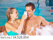 Glückliches Paar hat Spaß im Whirlpool mit Schaum im Spa. Стоковое фото, фотограф Zoonar.com/Robert Kneschke / age Fotostock / Фотобанк Лори