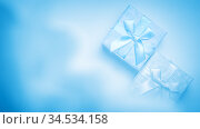 Christmas new year festive greeting banner poster for advertising or postcard, gift wrap, box with a bow of ribbons in the haze for the holiday on a blue snowy background with smoke top view, flatlay. Стоковое фото, фотограф Светлана Евграфова / Фотобанк Лори