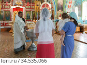 Women have ceremony of the Baptism of baby in the Orthodox church. The Priest prepares baptistery. It is sacrament of initiation into the Christian church (2020 год). Редакционное фото, фотограф Кекяляйнен Андрей / Фотобанк Лори