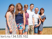 Four preteen children with their parents, large family portrait on wheat field, people standing shoulder to shoulder, looking at camera. Стоковое фото, фотограф Кекяляйнен Андрей / Фотобанк Лори