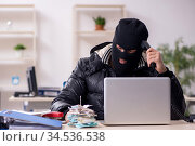 Young male burglar in the office. Стоковое фото, фотограф Elnur / Фотобанк Лори