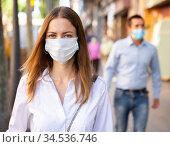 Woman wearing disposable face mask walking on street. Стоковое фото, фотограф Яков Филимонов / Фотобанк Лори