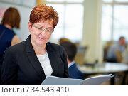 Ältere Frau im Büro liest sich ein Akte durch. Стоковое фото, фотограф Zoonar.com/Robert Kneschke / age Fotostock / Фотобанк Лори