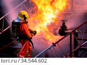 Firefighter using water fog type fire extinguisher to fighting with... Стоковое фото, фотограф Zoonar.com/Vichie81 / easy Fotostock / Фотобанк Лори