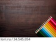 Multicolored pencils on the brown wooden table background. Стоковое фото, фотограф Zoonar.com/Ruslan Ropat / age Fotostock / Фотобанк Лори