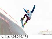 A skateboarder teenager in a hat does a trick with a jump on the ramp... Стоковое фото, фотограф Zoonar.com/Ian Iankovskii / easy Fotostock / Фотобанк Лори