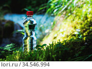 Transparent plastic A bottle of clean water with a red lid stands... Стоковое фото, фотограф Zoonar.com/Ian Iankovskii / easy Fotostock / Фотобанк Лори