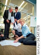 Geschäftsleute im Startup Unternehmen sortieren Papiere auf dem Boden. Стоковое фото, фотограф Zoonar.com/Robert Kneschke / age Fotostock / Фотобанк Лори