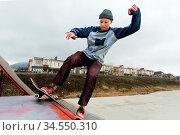 A teenager skateboarder in a hat does a Rocks trick on a ramp in a... Стоковое фото, фотограф Zoonar.com/Ian Iankovskii / easy Fotostock / Фотобанк Лори