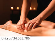 Close-up of male hands doing calf massage of female legs in a dark... Стоковое фото, фотограф Zoonar.com/Ian Iankovskii / easy Fotostock / Фотобанк Лори