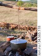 Metal cauldron hangs over a bonfire. Стоковое фото, фотограф EugeneSergeev / Фотобанк Лори