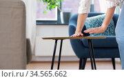 woman placing coffee table next to sofa at home. Стоковое видео, видеограф Syda Productions / Фотобанк Лори
