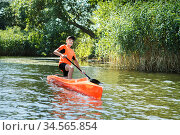 The boy rowing in a canoe on the river. Стоковое фото, фотограф Nataliia Zhekova / Фотобанк Лори