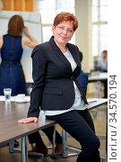 Ältere lächelnde Geschäftsfrau im Büro lehnt sich an einen Tisch. Стоковое фото, фотограф Zoonar.com/Robert Kneschke / age Fotostock / Фотобанк Лори