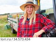 Jung Frau als Weinbauer oder Winzer Azubi lehnt an einem Traktor. Стоковое фото, фотограф Zoonar.com/Robert Kneschke / age Fotostock / Фотобанк Лори