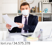 Manager in disposable mask discussing in office. Стоковое фото, фотограф Яков Филимонов / Фотобанк Лори