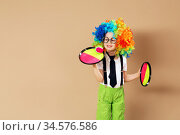 Blithesome children. Portrait of happy clown boy wearing large neon coloured wig. Стоковое фото, фотограф Nataliia Zhekova / Фотобанк Лори