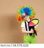 Kid in clown wig and eyeglasses playing catch ball game. Стоковое фото, фотограф Nataliia Zhekova / Фотобанк Лори