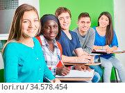 Multikulturelle Gruppe Schüler sitzt lächelnd in der Schule. Стоковое фото, фотограф Zoonar.com/Robert Kneschke / age Fotostock / Фотобанк Лори