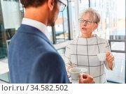 Ältere Geschäftsfrau trinkt einen Espresso beim Smalltalk mit einem... Стоковое фото, фотограф Zoonar.com/Robert Kneschke / age Fotostock / Фотобанк Лори