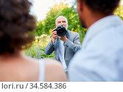 Hochzeitsfotograf und Brautpaar beim Fotoshooting in der Natur. Стоковое фото, фотограф Zoonar.com/Robert Kneschke / age Fotostock / Фотобанк Лори