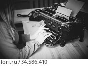 Secretary at old typewriter with telephone. Young woman using typewriter. Business concepts. Retro picture style. Стоковое фото, фотограф Nataliia Zhekova / Фотобанк Лори