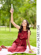 happy woman toasting drink at picnic in park. Стоковое фото, фотограф Syda Productions / Фотобанк Лори