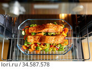 food cooking in baking dish in oven at home. Стоковое фото, фотограф Syda Productions / Фотобанк Лори