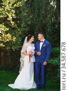 Just married loving hipster couple in wedding dress and suit in the park. Happy bride and groom walking in the beautiful garden. Romantic Married young family. Стоковое фото, фотограф Nataliia Zhekova / Фотобанк Лори