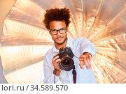 Kreativer junger Fotograf mit digitaler Kamera hat eine Idee beim... Стоковое фото, фотограф Zoonar.com/Robert Kneschke / age Fotostock / Фотобанк Лори