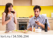 Young couple celebrating wedding anniversary at kitchen. Стоковое фото, фотограф Elnur / Фотобанк Лори
