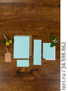 Notebook and blue sheet of papers surrounding by flowers on a wood table. Стоковое фото, агентство Wavebreak Media / Фотобанк Лори