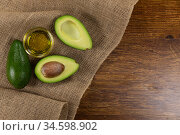 View of two avocados and olive oil bottle on wood table background. Стоковое фото, агентство Wavebreak Media / Фотобанк Лори