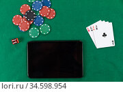 View of a black tablet, playing cards, a red dice and colorful tokens on plain green surface. Стоковое фото, агентство Wavebreak Media / Фотобанк Лори