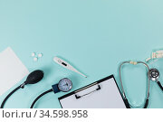 View of a composition with medical devices, pills and a folder with a sheet of paper on blue surface. Стоковое фото, агентство Wavebreak Media / Фотобанк Лори