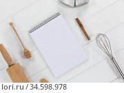View of a composition with a notebook with cookie cutters, whisker and rolling pin on a white wooden. Стоковое фото, агентство Wavebreak Media / Фотобанк Лори